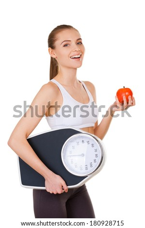 Leaving a healthy life. Side view of beautiful young woman in sports clothing holding weight scales and apple while standing isolated on white - stock photo