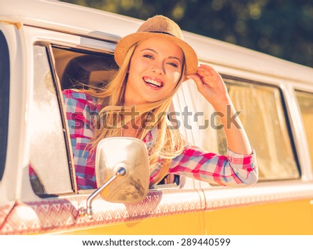 Leaving for the weekend. Cheerful young woman smiling at camera while looking through the vehicle window - stock photo