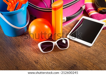 Leaving for vacations on the beach with digital tablet and colorful luggage and accessories. - stock photo