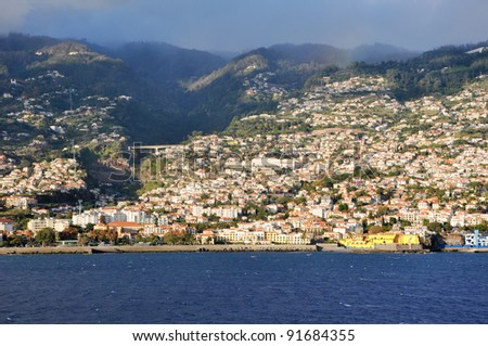 Leaving Funchal. View of capital city Funchal on madeira island, Portugal. Typical weather: sunny and cloudy - stock photo