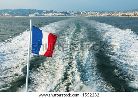 Leaving the Harbour in Cannes, France on a speedboat - French flag blowing in the wind - stock photo