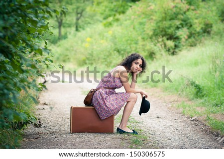 Leaving to an unknown destination: beautiful young woman waiting for her connection - stock photo