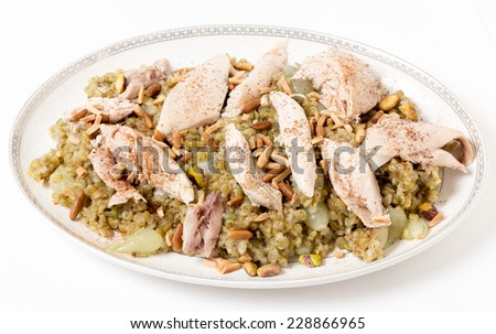 Lebanese cinnamon dusted chicken served on a bed of freekeh fire-dried green wheat with a garnish of toasted nuts. The grain, also spelt frikeh, has a low glycemic index and is high in fibre, - stock photo