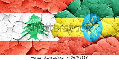 Lebanon flag with Ethiopia flag on a grunge cracked wall - stock photo