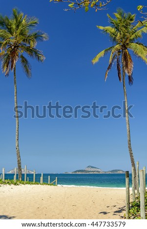 Leblon beach in the morning with the sea and the islands Cagarras among coconut trees