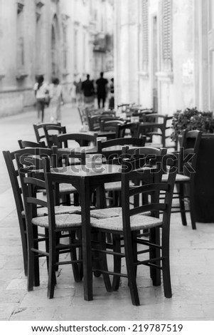 Lecce, IT, August 15, 2014: chairs and tables outside a bar. Horizontal black and white - stock photo