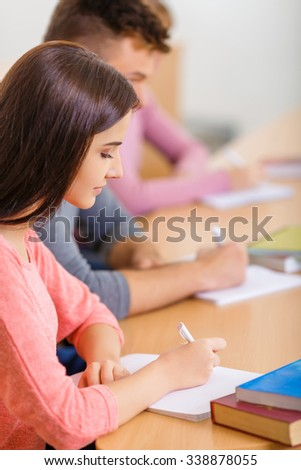 Lecture routine. Appealing young girl is sitting at the desk with her classmates and filling in her notebook. - stock photo