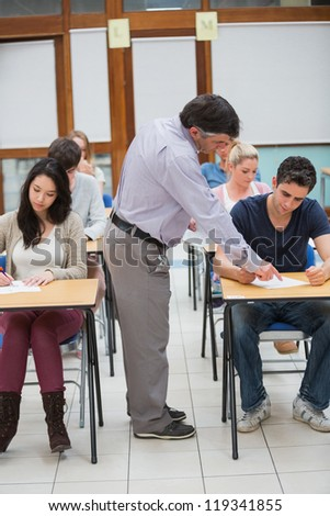 Lecturer helping student in classrom - stock photo