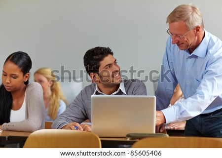 Lecturer talking to student in class at university - stock photo