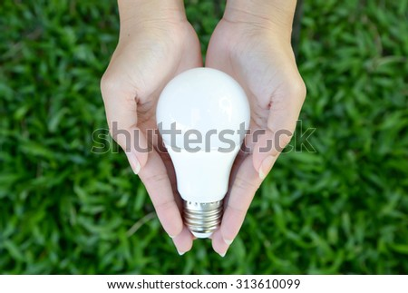 LED bulb in the human hand with green grass background - stock photo