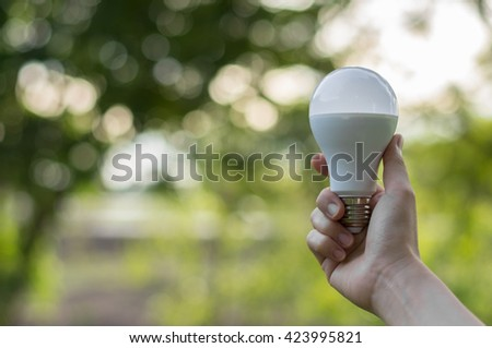 LED bulb,LED bulb in our hand of  beautiful woman green background,LED bulb - energy lighting in our control. - stock photo