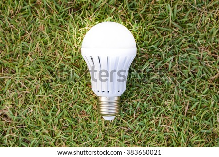LED Bulb with lighting on the green grass - stock photo