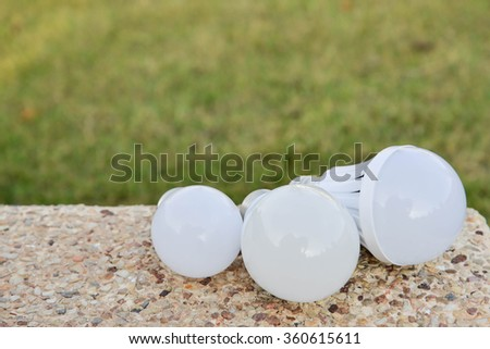 LED Bulbs - on the concrete with green grass background - stock photo