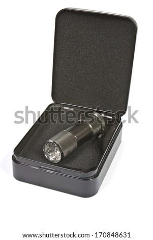 LED flashlight in a black metal box - stock photo