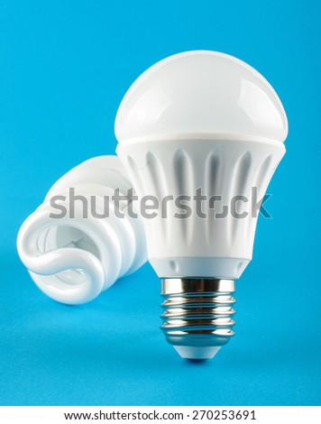 LED lamp in front of CFL lamp on the blue background - stock photo