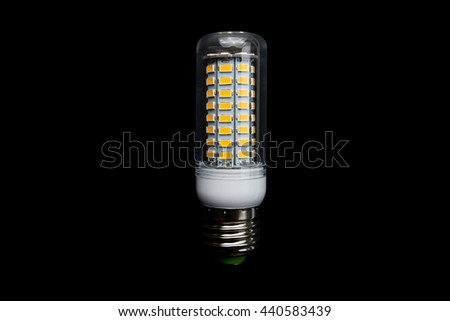 LED lamp on a black background in the form of maize with a lamp socket type E27 - stock photo