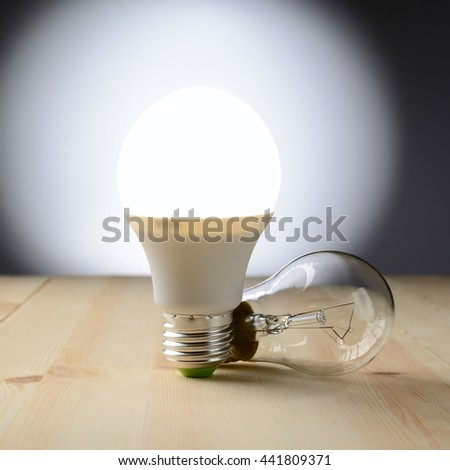 LED Lamp Standing On A Wooden Table, Near An Incandescent Lamp Lie