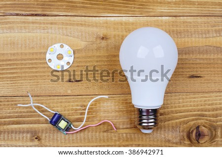 Led lamp with contacts and LED board on a wooden table. Job electrician. - stock photo