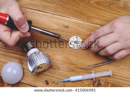 Led lamp with contacts and LED board on a wooden table. Job electrician. Male hands fixing the LEDs lamps. Workplace of electrician. Male electrician solder the LEDs lamp  - stock photo