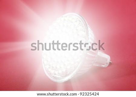 LED light bulb spot light on red background - stock photo
