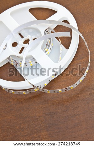 LED strip wound on a roll of brown wooden board - stock photo