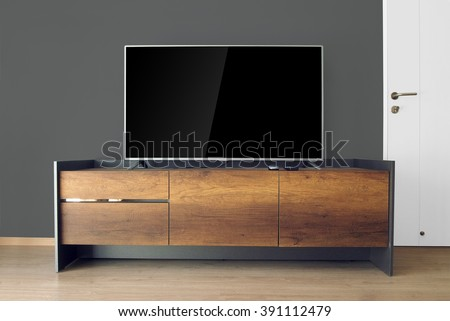 Led TV on TV stand in empty room with black wall. decorate in loft style. - stock photo