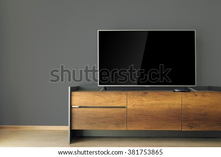 Led TV on TV stand with black wall - stock photo