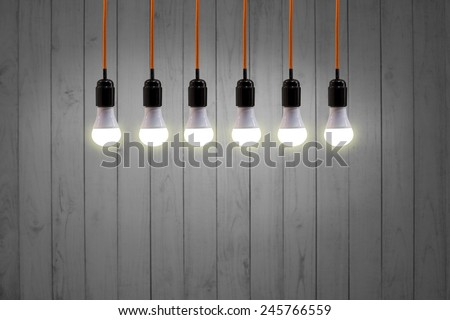 LED vintage hanging energy light bulbs on wooden wall retro, background - stock photo
