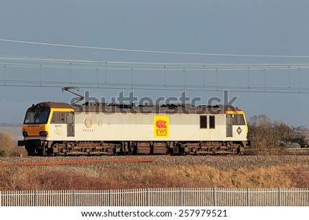 LEDBURN, UK - FEBRUARY 20: A class 92 EWS branded electric loco passes Ledburn Jn light while on route to Willesden depot on February 20, 2015 in Ledburn. EWS were sold to DBS in 2007 for £309Mn. - stock photo