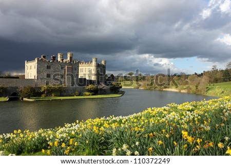 Leeds Castle in Kent, United Kingdom with blooming daffodils and dramatic sky. - stock photo