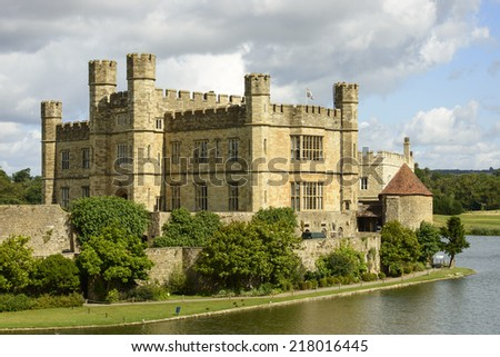 Leeds castle main building, Maidstone, England view of the main building of medieval castle and its moat,  shot in bright light under a cloudy sky  - stock photo