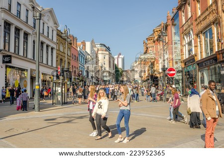 Leeds, UK - September 28, 2014: Shoppers on Briggate Street on a clear Autumn Day. Briggate is one of the pedestrianised principal shopping streets in central Leeds.  - stock photo