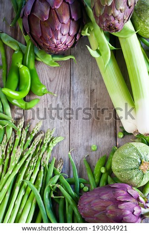 Leek, artichoke, beans, zucchini, pea on old wooden planks. Background with empty center. - stock photo