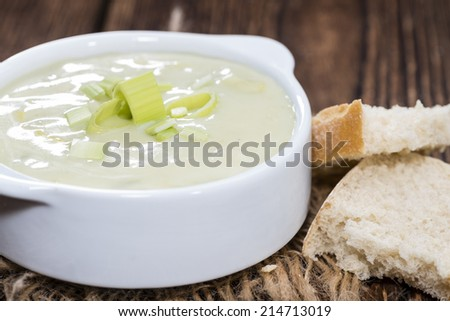 Leek Soup (fresh made) in a bowl on wooden background