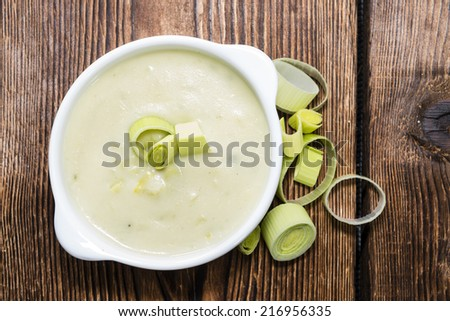 Leek Soup (fresh made) in a bowl on wooden background - stock photo