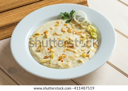 Leek vegetable soup cream in white plate with almond flakes - stock photo