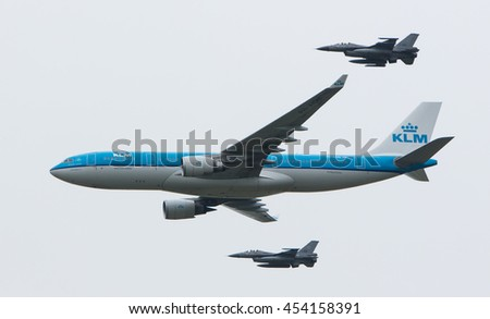 LEEUWARDEN, NETHERLANDS - JUNE 11 2016: Dutch KLM Boeing escorted by two F16 fighter jets of the Dutch air force on juni 11 , 2016 in Leeuwarden. - stock photo