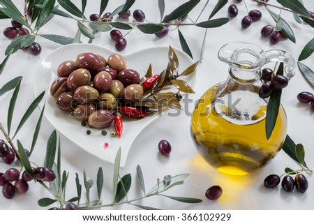 Left a white heart shape plate of green olives garnished with a sprig of bay leaf, red peppers, a bottle of olive oil on the right framed by olive tree branches on a white background. Olives and oil.  - stock photo