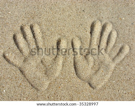 Left and right handprints on a sand. - stock photo