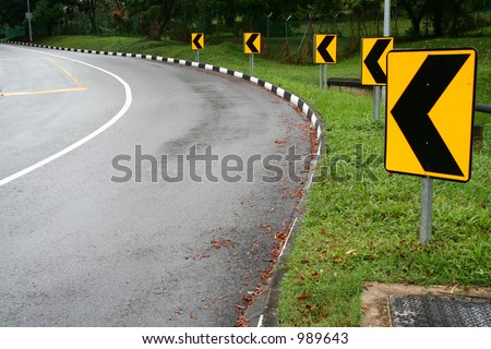 Left arrow Street signs around the bend of a road - stock photo