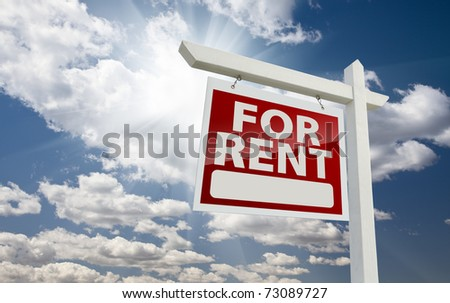 Left Facing For Rent Real Estate Sign Over Clouds and Sunny Sky with Room for Text. - stock photo