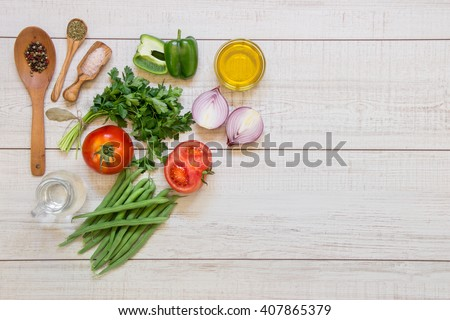 Left fresh vegetables ready to cook tomatoes, peppers, green beans, onions, parsley, spices in wooden spoons on light wood background, right empty space. Vegetables ingredients. Horizontal.Top view.   - stock photo