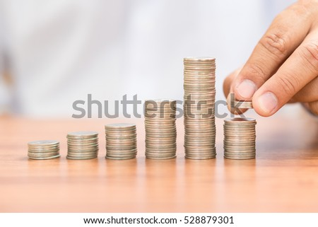 Left hand add coin to coin stack, saving money concept.
