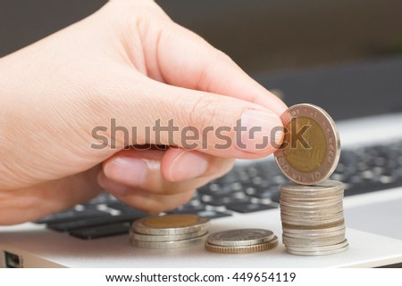 Left hand and pile of coins.