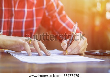 left hand Businessperson Signing Contract,Man writing paper at the desk, man writing with pen and reading books at table,man Signing, Form. in office,vintage tone ,morning light ,selective focus. - stock photo