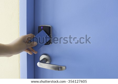 left hand hold key card touch on black electronic pad lock access control with stainless steel door handle on blue door - stock photo