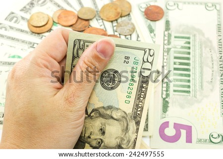 Left  hand holding dollar bill with coins and dollar bill are background. - stock photo