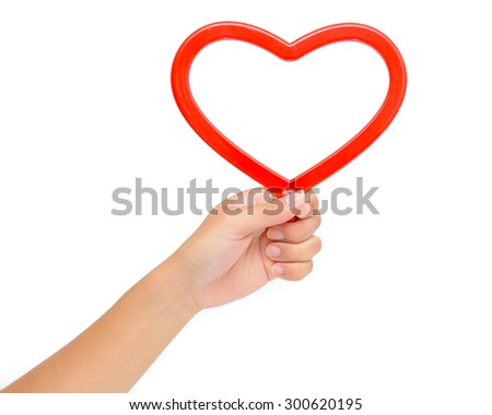 Left hand holding red heart with copy space - stock photo