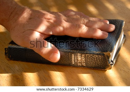 Left Hand On Bible For Testimonial Oath, Under Dramatic Light - stock photo