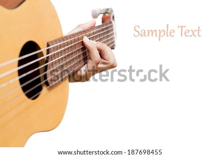 Left hand plays chord on acoustic guitar, isolated - stock photo